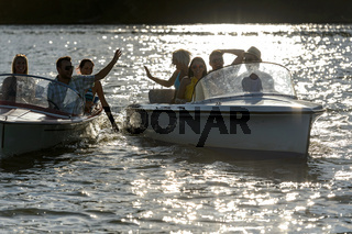 Silhouette of young friends in motorboats