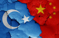 flags of East Turkestan and China painted on cracked wall