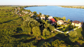Drone fly over waving river of blue color surrounded by local village with various buildings and Wetland and marsh habitat with a reedbed of Common Reed aerial view.