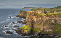 Dunluce Castle illuminated by sunlight, perched on the edge of cliff, Northern Ireland