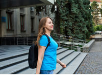 The happy female student with backpack leaves university