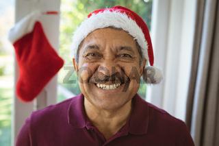 Portrait of happy biracial senior man in santa hat at christmas