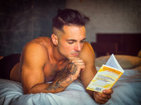 Sexy young man shirtless on bed reading a book