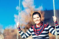 happy woman on a swing in landscape.