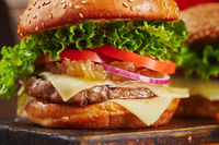 Appetizing homemade burger with beef, cheese and onion marmalade close-up. Fast food concept, american food