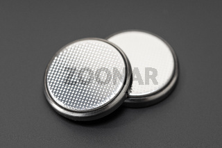Button cell battery or coin cell isolated on black background