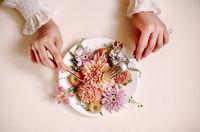 Crop woman eating fresh flowers