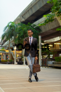 Full length portrait of handsome young African businessman outdoors in city using mobile phone