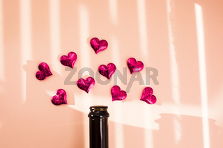Bottle of wine and pink hearts over morning shadow overlay.