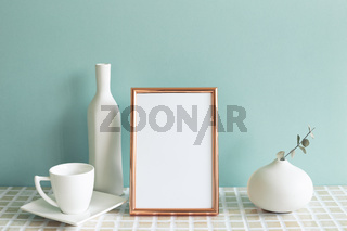 Photo frame and white coffee cup, vase on mosaic tile table. mint wall background. home interior
