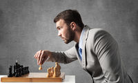 Concentrated businessman playing chess game