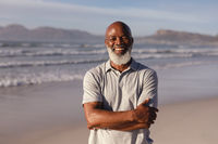 Portrait of senior african american man with arms crossed smiling while standing on the beach