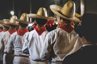 Men with traditional Mexican clothing and straw hats lining up before performance, Merida, Mexico