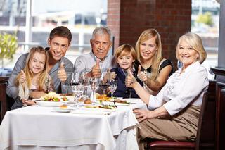 Familie im Restaurant hält die Daumen hoch