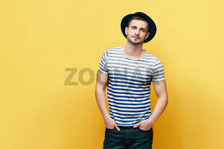 Fashion portrait of young hipster man in hat over yellow background