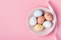 Colorful chocolate easter eggs. Sweet candy eggs on pink background.