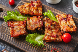 Grilled baked pork ribs with spices and vegetables on wooden cutting board on dark background. American food concept.