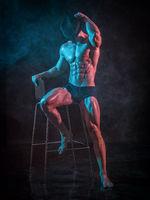 Shirtless muscular bodybuilder sitting on stool wearing hat