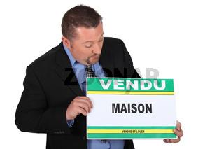 Estate agent holding sold sign