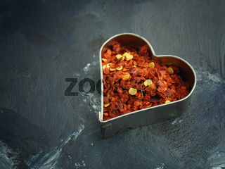 Hot organic chili flakes in a heart shaped cookie cutter