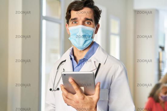 Arzt mit Mund-Nasen-Schutz wegen Covid-19 und Tablet PC