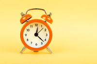 Close up one orange alarm clock over yellow background