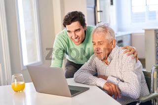 Sohn unterstützt seinen Vater am Laptop Computer zu Hause