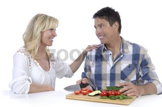 Glückliches reifes Ehepaar beim Gemüseschneiden