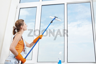 Attractive young girl washes windows