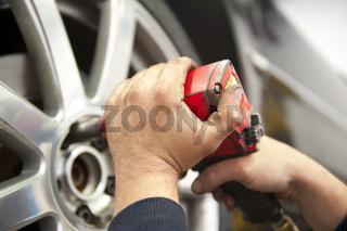 Mechanic changing car tyre in garage