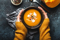 Female hands with bowl of pumpkin soup