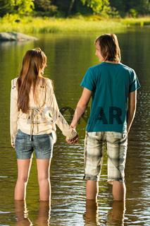 Teenage couple standing in water holding hands