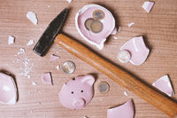 broken Piggy bank smashed into pieces with hammer and small change