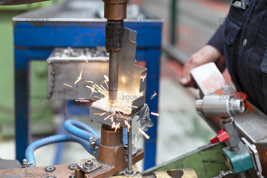 Close up of a metal element being spot-welded by a factory worker. Industry concept.