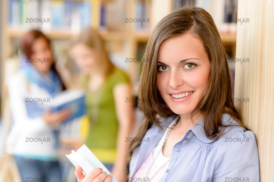 Teenage student with book at school library