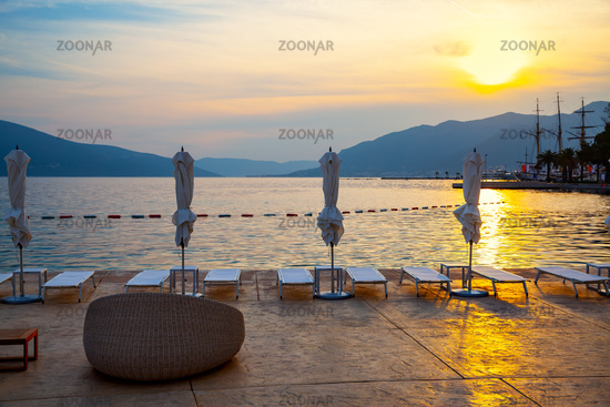 Terrace on the sea beach by the at sunset