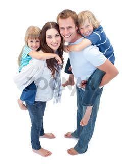 Loving family enjoying piggyback ride against a white background
