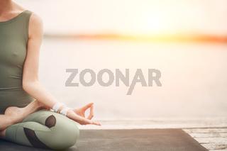 Yoga symbol. Lotus pose at the lake on sunset. Stylish modern woman
