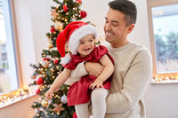 happy father and baby girl over christmas tree