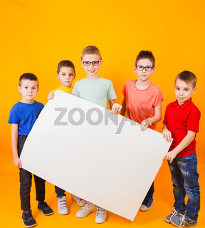 The happy different boys are holding a large white paper