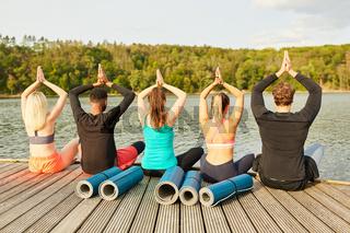 Freunde am Seeufer machen eine Yoga Übung