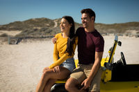 Happy caucasian couple sitting on beach buggy by the sea smiling