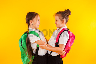 Two smiling schoolgirls in uniform are hugging at the yellow