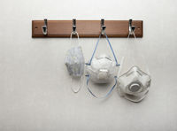 Several respirator masks hanging on clothes rack