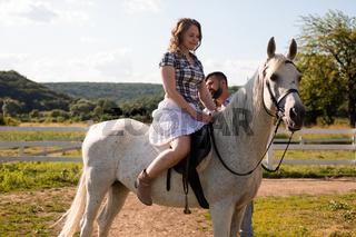 The man teaches a woman to ride a horse