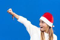 Joyful Young girl in Santa hat gesturing on blue background.