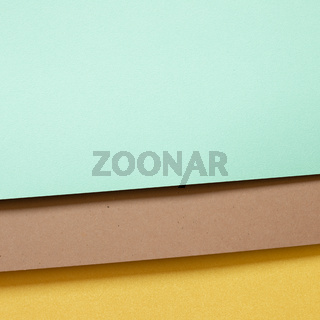 Mint blue and brown and yellow layered color paper background. top view