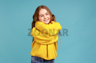 Portrait of charming little girl embracing herself and smiling from happiness, positive self-esteem.