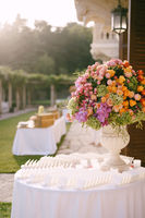 Wedding dinner table reception. A huge bouquet in an old marble vase of pink, red, orange and yellow roses, green hydrangeas, purple orchids. Stands on a round table with maps of seating guests.