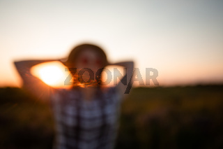 Blurred image of a young girl on sunset sky background
